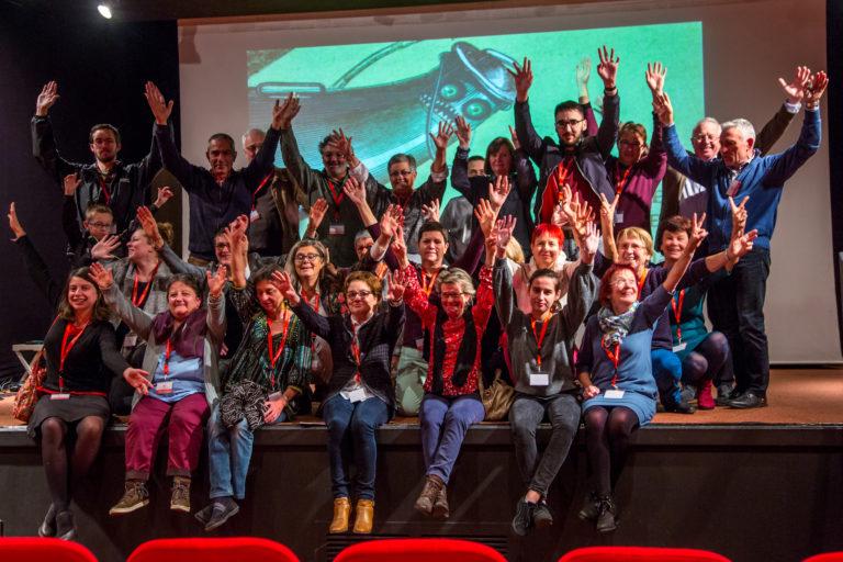 Assis et debouts sur la scène de la Salamandre, les bénévoles du LEC Festival posent pour la photo avec le sourire et les bras levés !